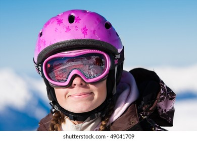 Smiling young girl wearing ski mask and helmet. Winter sport vacation