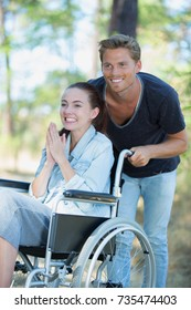 smiling young girl in wheelchair playing with her boyfriend outdoor