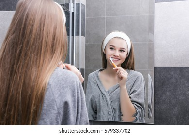 Smiling young girl with white teeth in white bandage on head, looking in the mirror and brush your teeth. Girl in grey robe in bathroom near white washbasin to do cosmetology procedure