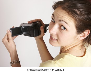 Smiling young girl with yellow t-shirt looking back over shoulder holding video recorder