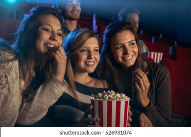 Smiling young girls sitting at the cinema, watching a film and eating popcorn, friendship and entertainment concept