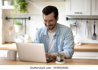 Smiling young guy in glasses enjoying online communication, typing message in social networks on computer. Happy millennial male client involved in using software application, people and technology.