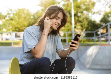 Smiling young guy spending time at the skate park, listening to music with earphones