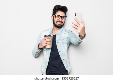Smiling young guy taking selfie photo on smartphone. Indian man using digital device. Selfie photo concept. Isolated front view on white background.