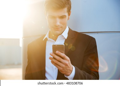 Smiling young handsome businessman using mobile phone outdoors leaning at the wall
