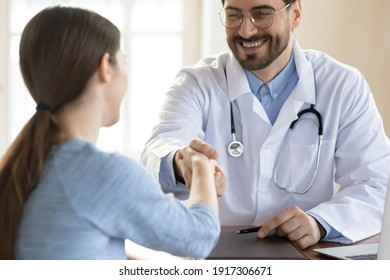 Smiling young handsome male doctor in eyeglasses and uniform shaking hands with female client, celebrating signing medical insurance contract or welcoming patient at checkup meeting in clinic office.