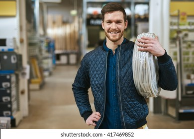 Smiling young handyman with a roll of cable over his shoulder grinning at the camera as he makes a purchase in a hardware store