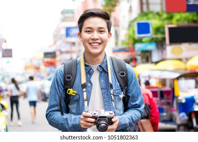 Smiling young happy Asian male tourist photographer backpacking in Khao san road,  Bangkok, Thailand on vacations