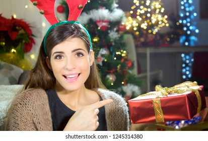 Smiling young happy woman showing christmas present