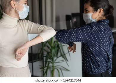 Smiling young healthy mixed race female colleagues wearing facial medical masks greeting each other by bumping elbows gesture at workplace keeping social distance, preventing spreading covid19 virus.