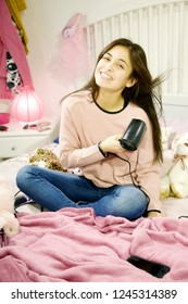 smiling young hispanic woman who dries her long hair in her bedroom
