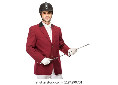 smiling young horseman in uniform holding horseman stick and looking at camera isolated on white