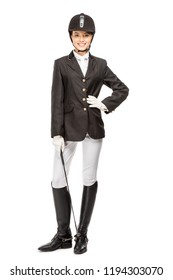 smiling young horsewoman in uniform holding horseman stick and looking at camera isolated on white