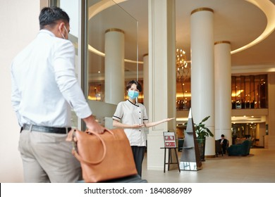 Smiling young hotel concierge making welcoming gesture and inviting guest inside