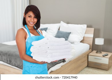 Smiling Young Hotel Maid Bringing Fresh Clean Towels In The Room