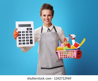 smiling young housemaid in apron with a basket with cleansers and brushes showing big calculator on blue background. Do not think that cleaning service is a luxury. Calculate your time correctly