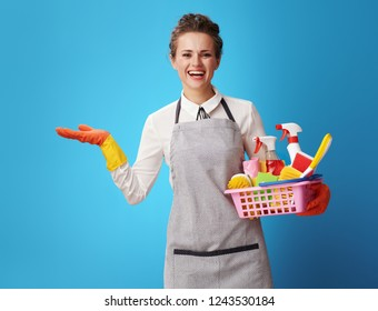 smiling young housemaid in apron with a basket with detergents and brushes presenting something on empty palm isolated on blue. female cleaning expert provides reliable and efficient cleaning company
