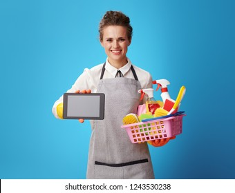 smiling young housemaid in apron with a basket with detergents and brushes showing tablet PC blank screen isolated on blue. Housemaid shows app on the tablet PC for an easy ordering cleaning service