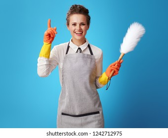 smiling young housemaid in apron with dust cleaning brush got idea against blue background. Where cleaning start? Quality - with the call of professionals in their field. cleaning service workers
