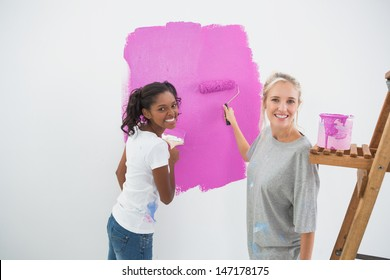 Smiling young housemates painting wall pink in their new home looking at camera