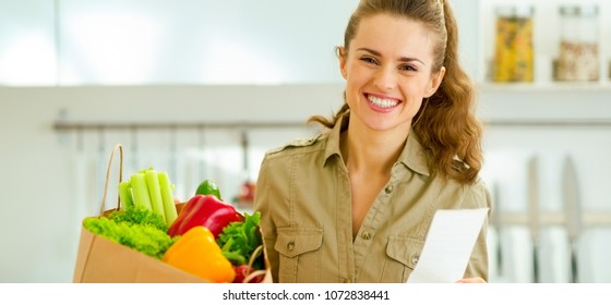Smiling young housewife with check and shopping bag full of vegetables