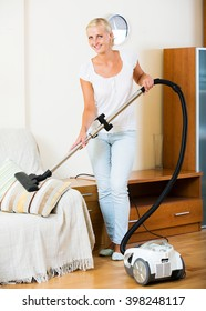 Smiling young housewife in jeans vacuuming floor and furniture