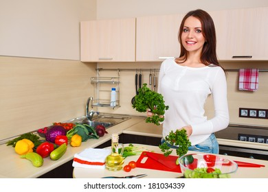 Smiling young housewife mixing fresh salad