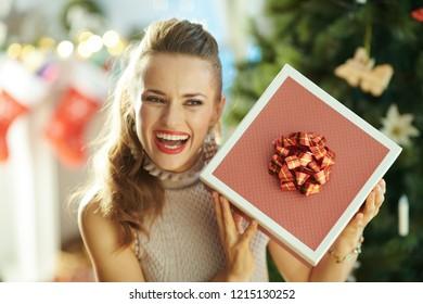 smiling young housewife near Christmas tree shaking Christmas present box