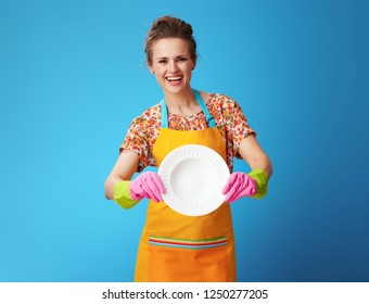 smiling young housewife in orange apron showing washed plate against blue background. Who better washing dishes - a housewife or a dishwasher?