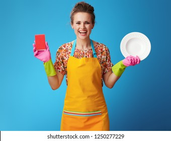 smiling young housewife in orange apron with sponge and plate isolated on blue background. Dirty dishes - can not be in a clean house. Every experienced housewife knows this.
