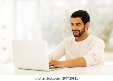 smiling young indian man using laptop at home