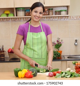 Smiling young Indian woman cutting vegetables