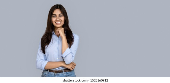 Smiling young indian woman girl teacher stand isolated on grey background banner. Happy lady female sales office professional employee customer looking at camera, student business portrait
