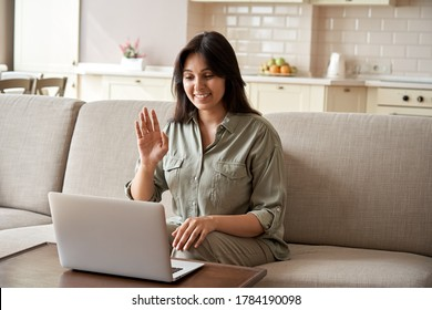 Smiling young indian woman video calling using laptop webcam conference work at home office. Happy lady sit on sofa talk by virtual videoconference meeting dating online using computer app videocall.