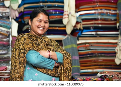 smiling young indian woman weaver at whool shawl shop clothing