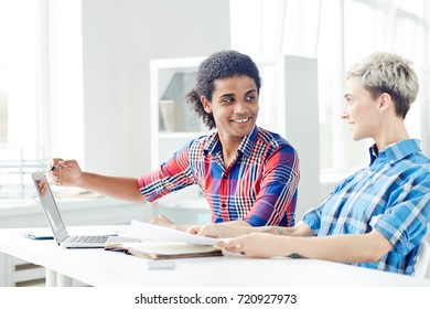 Smiling young interior designers wearing checked shirts working together on joint project while sitting at desk in spacious open plan office, handsome mixed race man pointing at laptop screen