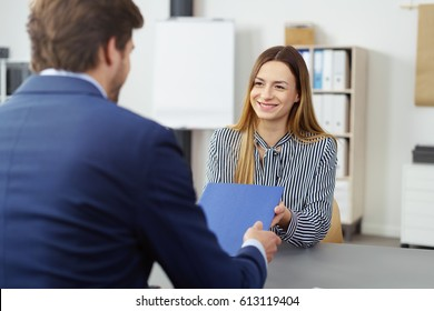 Smiling young job applicant in an interview for employment handing over her CV in a blue folder to the personnel office or manager