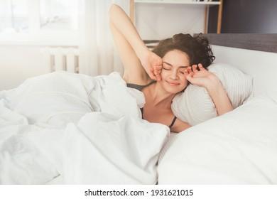 Junge Dame wach nach gesundem Schlaf und in gemütlichem, komfortablen Schlafzimmer-Interieur bei gutem Morgen. Glückliches Konzept