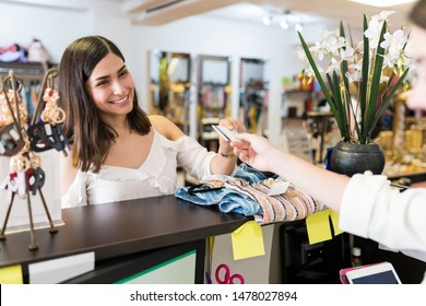 Smiling young Latin woman paying through credit card at checkout in clothing store