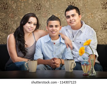 Smiling young Latino family of three sitting together
