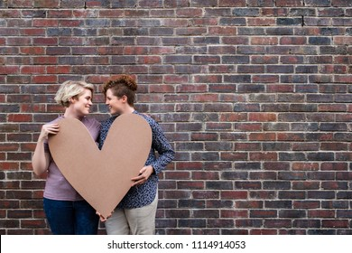 Smiling young lesbian couple looking at each other while standing together outside in front of a brick wall holding a heart symbol
