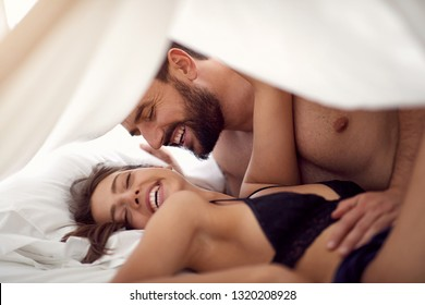Smiling young lovers making love in bedroom