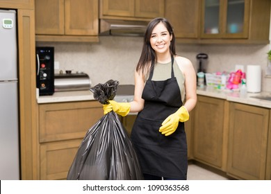 Smiling young maid wearing black apron and yellow latex rubber gloves standing in kitchen holding black plastic garbage bag