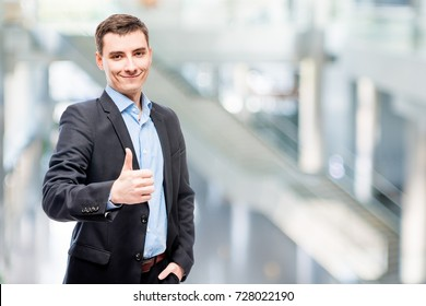 Smiling young male business executive in office portrait