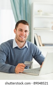 Smiling young male with credit card at his notebook