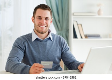 Smiling young male with credit card at his laptop