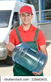 Smiling young male delivery courier man in front of cargo van delivering bottles of water