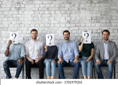 Smiling young male job candidates sit on chair in queue with unknown people holding sheets with question mark, happy hired man chosen among work applicants, employment, recruitment concept