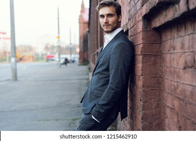 Smiling young male manager formal dressed leaning on a wall outdoors