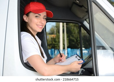 Smiling young male postal delivery courier man in front of cargo van delivering box